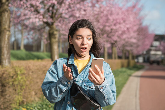 shocked face expression of a mixed races woman looking into the phone while walking on the street in bloomy spring
