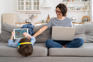 Fototapeta Family, quarantine, distance job concept. Happy mother freelancer remote work from home office on laptop during lockdown, sitting on couch, little son playing on digital tablet and wear headphones.  obraz