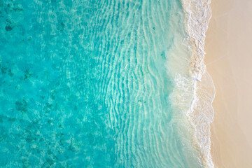 Top view on coast waves on beach aerial view, crystal clear water. Stunning summer landscape, sunny tropical island shore. Seaside, idyllic nature Earth view. Stunning scenery, amazing view - fototapety na wymiar