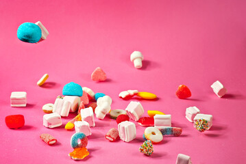 Lots of colorful candies on a pink background. Sweets close up. The concept of childhood and holidays.