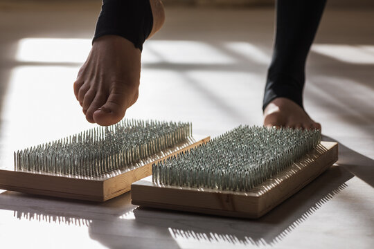 A woman practicing yoga steps on a board with nails. Concept on the topic of massage