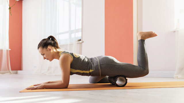 A woman in sportswear on a mat, performs a myofascial massage of the thigh with a roller, muscle recovery after injuries