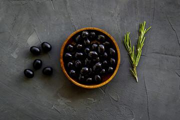 Wooden bowl of pickled black olives, top view