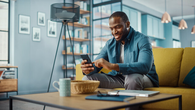 Handsome Black African American Man Using Smartphone while Sitting on a Sofa in Cozy Living Room. Freelancer Working From Home. Browsing Internet, Using Social Networks, Having Fun in Flat.