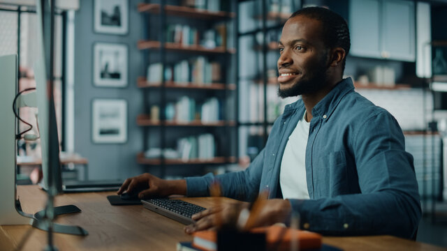 Handsome Black African American Specialist Working on Desktop Computer in Creative Home Living Room. Freelance Male is Working on a Finance Presentation Report for Clients and Employer.