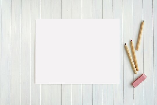 Blank horizontal paper sheet and pencils on wooden background, US letter size coloring page, stationery mockup, back to school, education, drawing concept.