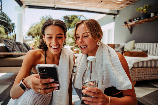 Two mixed race female friends smiling looking down on cellular device