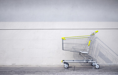 shopping cart parked gray brick wall outside a supermarket. space for text