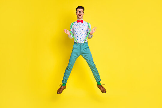Full size photo of young excited man happy positive smile have fun jump up isolated over yellow color background