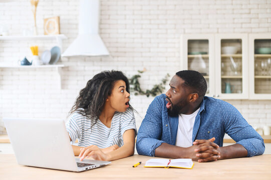 Shocked multiracial couple feel euphoric sitting at the laptop at home in the modern kitchen, looking at each other opened mouthes, found out unexpected good news, got online sale offer or discount