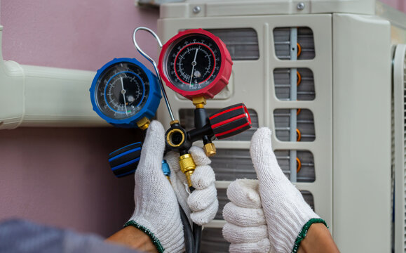 Technician man giving thumb up with holding refrigerant manifold gauge set air conditioning tools with hose and hook, repairman fixing air conditioning system, Air Conditioning Repair Concepts