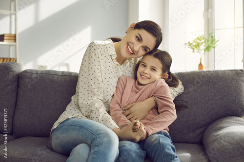 Portrait of a smiling young mother hugging her little daughter sitting on sofa at home. Woman having fun with her baby. Mother's Day, love, family, motherhood, and childhood concept.