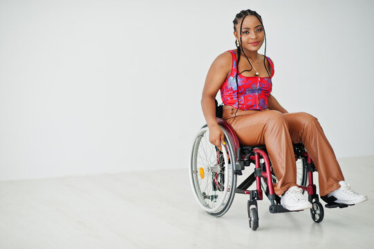Young disabled African American woman in wheelchair against white wall.