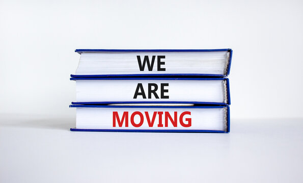We are moving symbol. Books with words 'We are moving'. Beautiful white background. Business, we are moving concept, copy space.