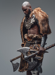 Fototapeta Portrait of a black skinned wild man with two huge axes in gray background