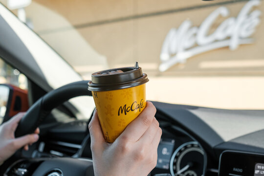 Woman sitting in the car and drinking coffee from McCafe, April 2021, Prague, Czech Republic.