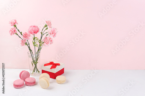 Colorful macaroons and flowers on a light table, festive food for mother's day, wedding, birthday. Modern bakery concept, selective focus, delicious dessert. Business card for a restaurant or cafe