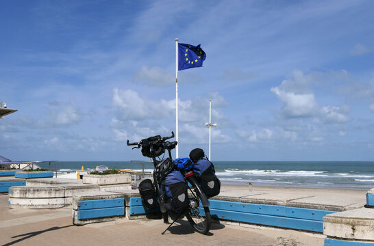 A packed touring bike on the French coast in front of a waving European flag.