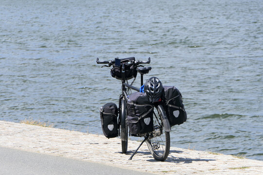 Break by the sea. A fully packed touring bike stands by the sea and waits for the driver.