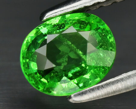 Natural gemstone green tsavorite garnet on background