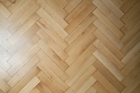 Classic old wooden parquet laying in the form of a herringbone in light brown color. Imeless classics in the design of the floor in the house.