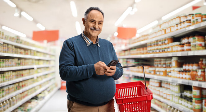 Man holding a shopping basket and a mobile phone inside a supermarket and looking at camera