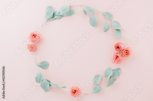 Flowers composition. Wreath made of rose flowers, eucalyptus branches on pastel pink background. Flat lay, top view, copy space. Mother's day card