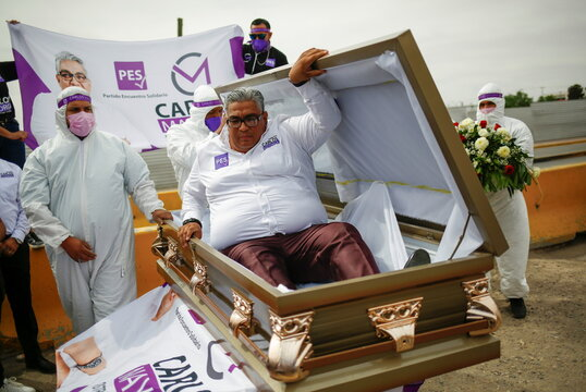 """Carlos Mayorga, Mexican candidate for federal representative, emerges from a coffin as part of his campaign slogan """"If I don't deliver, let them bury me alive"""" near the Zaragoza-Ysleta international border bridge, in Ciudad Juarez"""
