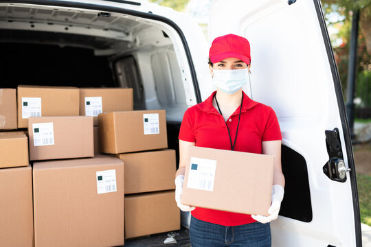 Beautiful young woman with a face mask delivering a package