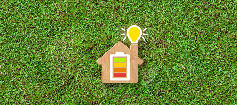 Energy efficiency and rating chart in a small model house with glowing lightbulb in the chimney over green grass in an ecological and environmental concept