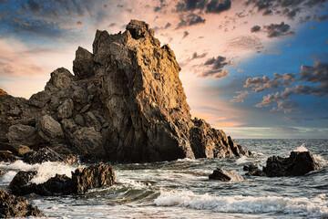 Obraz sunset on the beach with a huge rock - fototapety do salonu