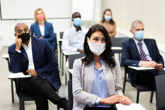 Group of business people in protective masks of different nationalities at business seminar