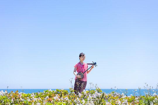 海辺で三線を弾く日本人女性