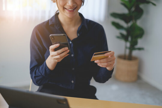 Woman in casual shirt paying with credit card online while making orders via application on cell phone. Successful and happy business woman making transaction using mobile bank application.
