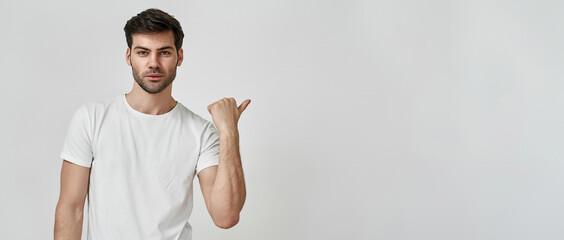 Fototapeta Man wearing t-shirt pointing thumb aside