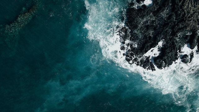 Aerial shot of waves crashing into a Hawaiian lava rock coast. drone