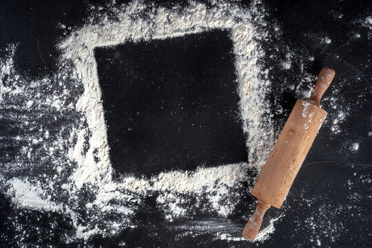 Baking frame with copy space, white flour and a wooden rolling pin