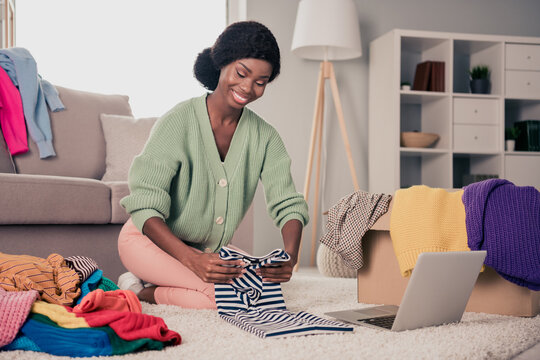 Full size photo of young afro woman prepare for sale auction charity pack her used dressing clothes pile stack sit floor laptop home