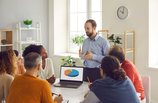 Business team leader making presentation standing at table in group office meeting, showing project statistics or feedback report circle charts on laptop screen and motivating employees to work better