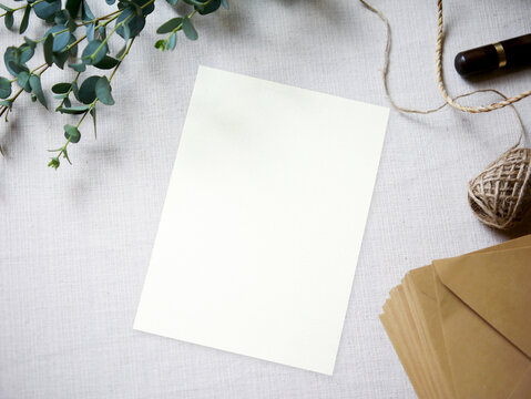Top view mockup blank card, for greeting, wedding invitation template with eucalyptus leaves on cloth background. with clipping path.