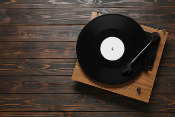 Fototapeta Turntable with vinyl record on wooden background, top view. Space for text