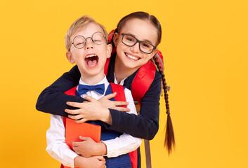 Fototapeta Happy schoolgirl giving piggyback ride to boy