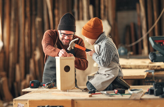 Kid with dad assembling wooden bird house in craft workshop
