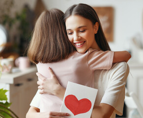 Grateful mother with card hugging daughter