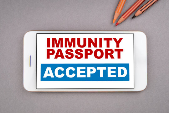 IMMUNITY PASSPORT ACCEPTED. Lifting restrictions and free travel concept. Mobile phone on a gray background