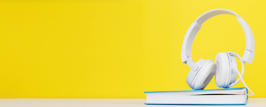 Audio book concept with modern white headphones and hardcover book on a yellow background. Listening to a book.