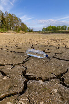 A bottle of water on the dried ground. The concept  of thirst, dehydration.