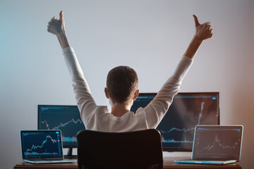 Fototapeta successful male trader looking at monitor with stock exchange graph or chart