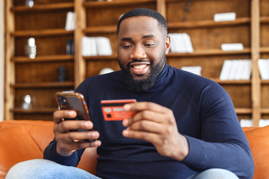 Smiling African-American man shopping online sitting on the sofa at home, holding credit card and smartphone, dark skinned multiracial guy making food order, purchasing online, booking and paying