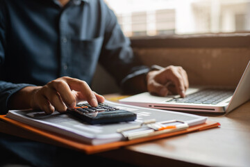 Fototapeta Hand businessman doing finances and calculate on desk about cost at office. obraz